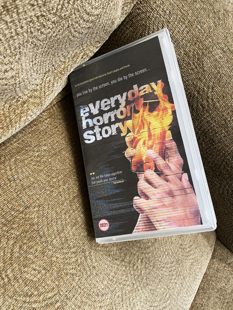 vhs cassette with the title 'everyday horror story' in a brown armchair
